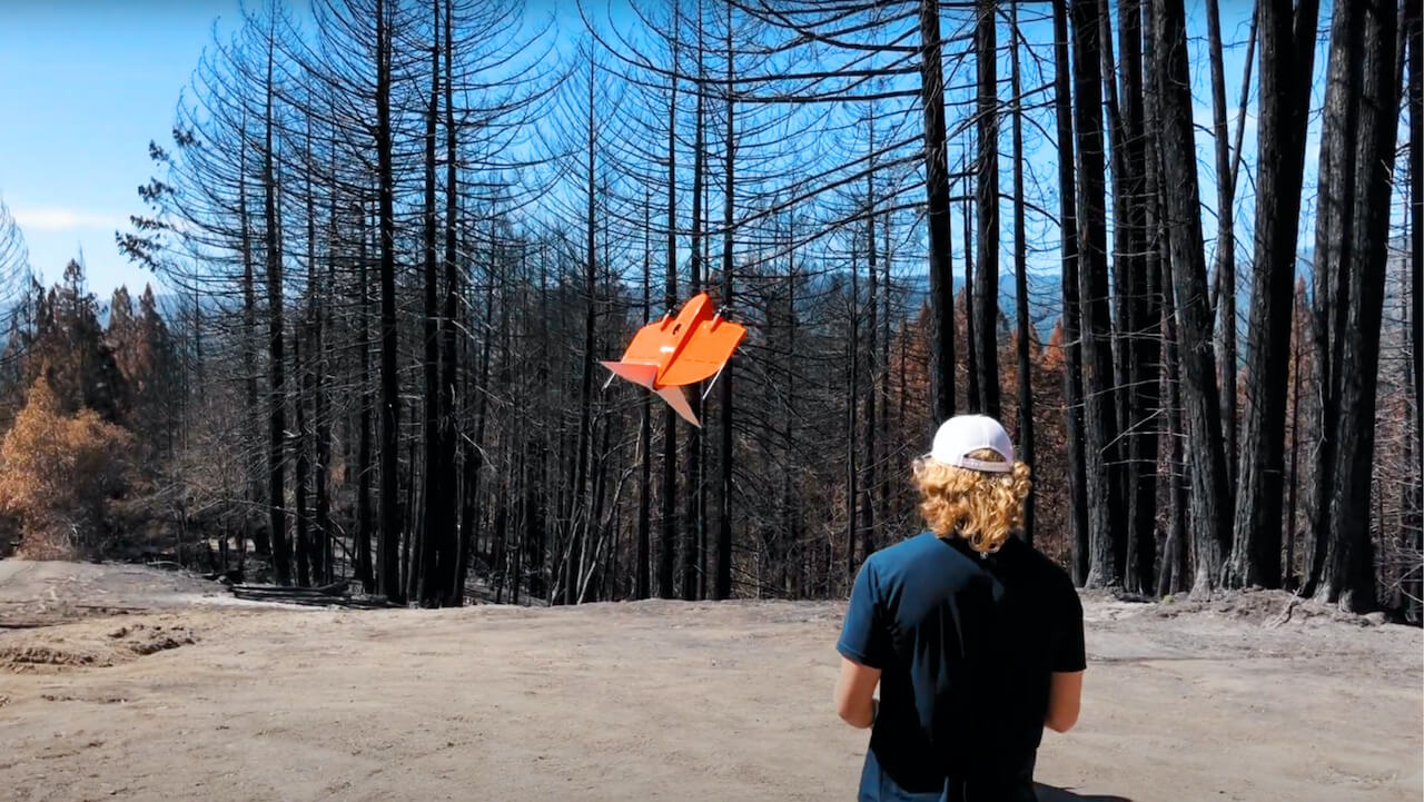 Pilot flying WingtraOne in the redwood forest plus video play button