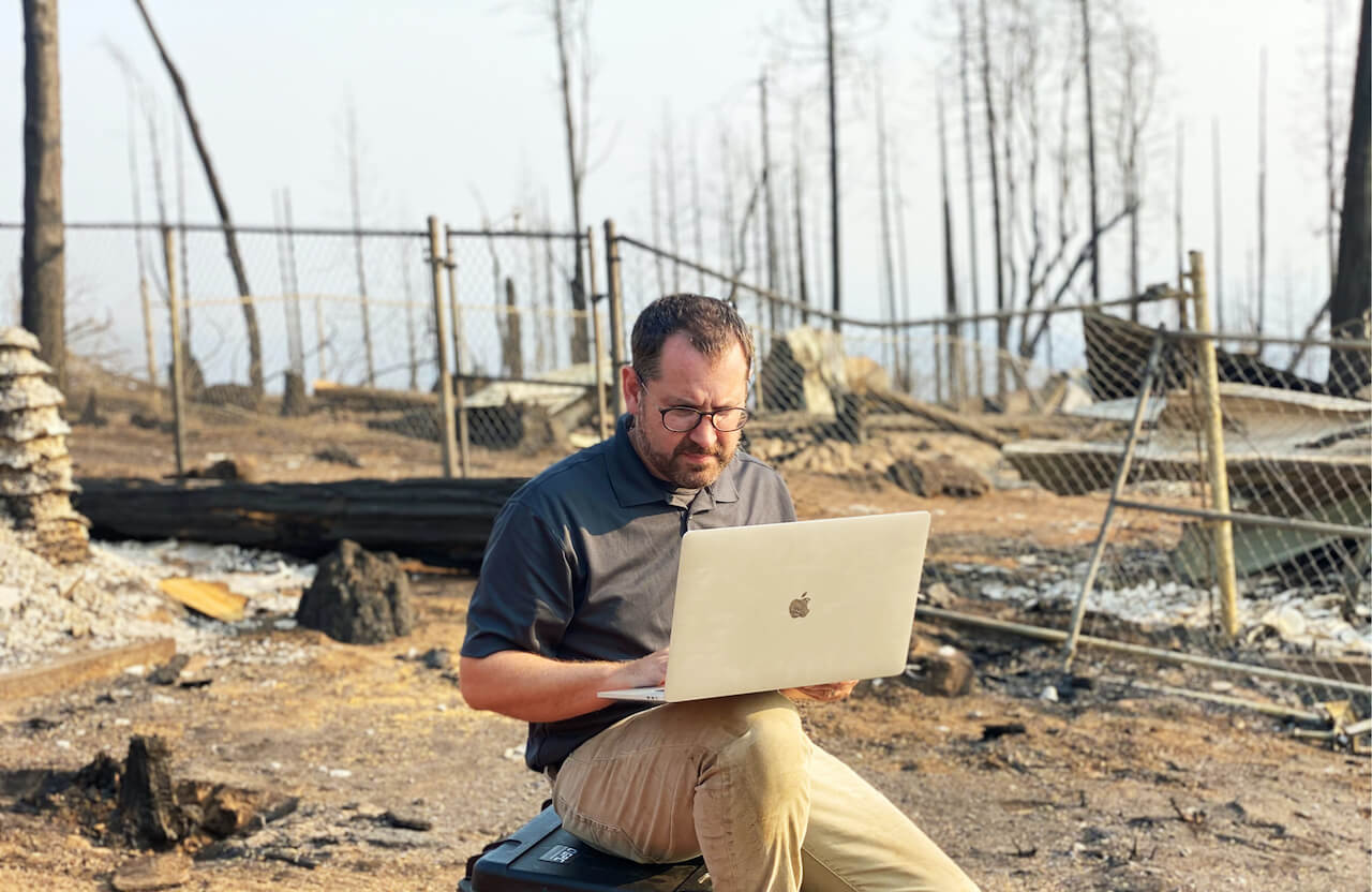 Dr. Greg Crutsinger working on a laptop in the middle of a burned out forest