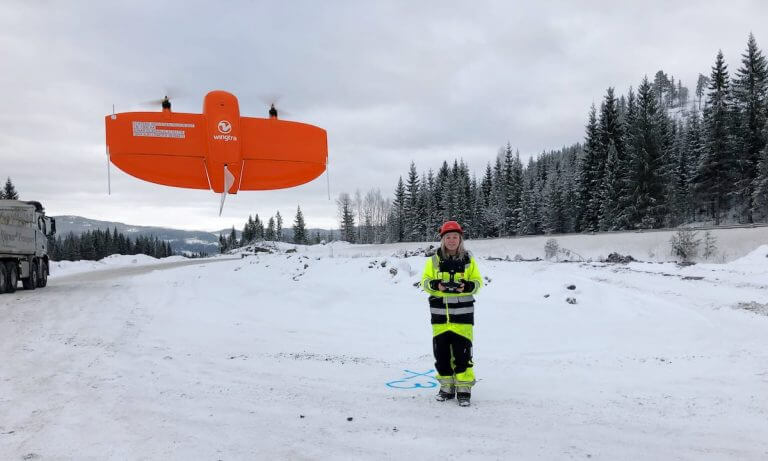 Engineer flying WingtraOne drone over a road