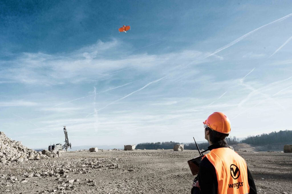 Field operator flying WingtraOne from a gravel terrain site